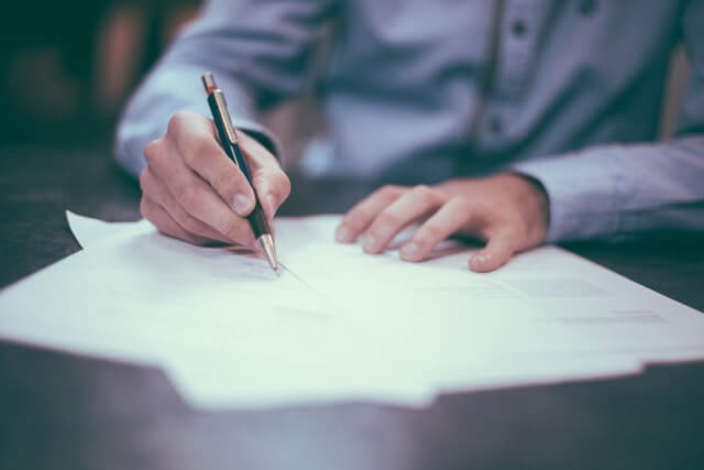 man signing a business shareholders agreement